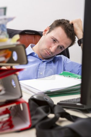 Photo for Office businessman at his desk full of documents, showing an overwhelmed expression. - Royalty Free Image