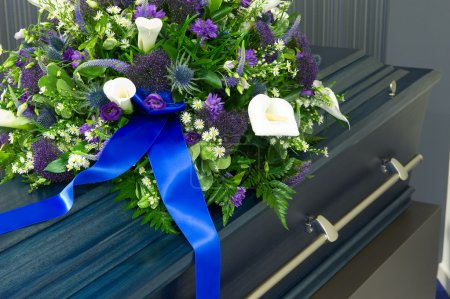 A blue coffin in a morgue with a flower arrangemen...