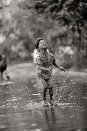 Photo pour Sous une pluie d'été, le garçon se promène et saute sur les piscines - image libre de droit