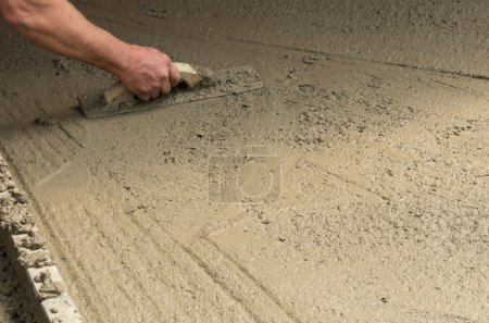 Worker finishing a concrete floor