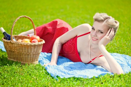 Young blond woman is lying on grass