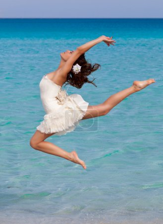 A woman is dancing on the beach