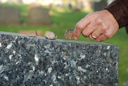 Photo pour Main d'homme plaçant une pierre sur une pierre tombale dans un cimetière . - image libre de droit