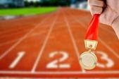 Athletic holding golden medal