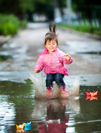 Photo for Happy little girl, wearing a pink jacket, jumps into a puddle - Royalty Free Image