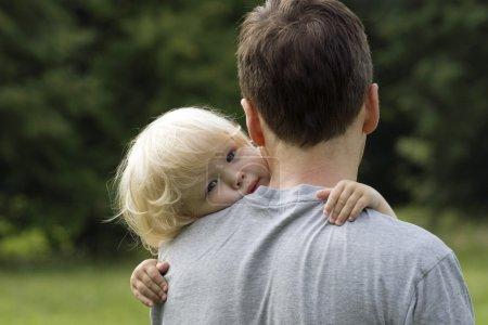 Little boy hugging hugging father around shoulders