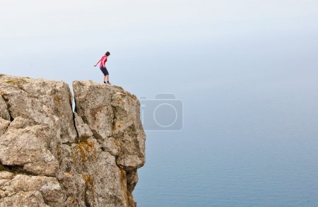 Lonely woman standing on the edge of the cliff