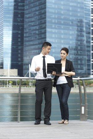 Photo pour Asiatique homme d'affaires et femme à l'aide d'un ordinateur portable à l'extérieur - image libre de droit