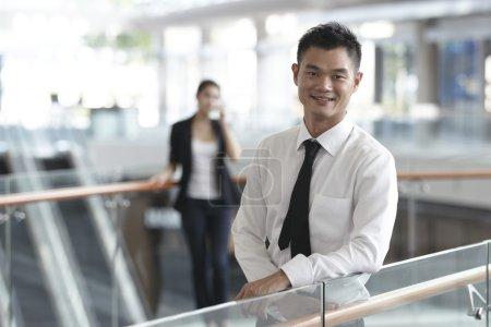 Photo pour Asiatique homme d'affaires avec collègue en arrière-plan - image libre de droit