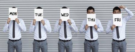 Photo pour Image conceptuelle de la semaine de travail. Asiatique homme d'affaires tenant des signes avec les jours de la semaine écrit sur eux . - image libre de droit