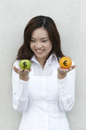 Photo for A conceptual image about choice. The Asian woman holding an apple and orange with US and Euro symbols drawn on them. - Royalty Free Image