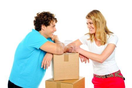 Photo pour Aimable jeune couple souriant avec des boîtes se regardant dans les yeux. Concept d'amour - image libre de droit