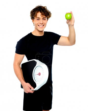 Fit guy with weighing scale and green apple