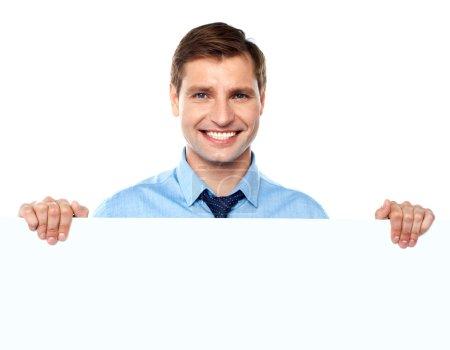 Photo pour Entrepreneur souriant promouvant grande bannière vierge annonce isolée sur blanc - image libre de droit