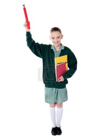 Pretty girl showing pencil upwards