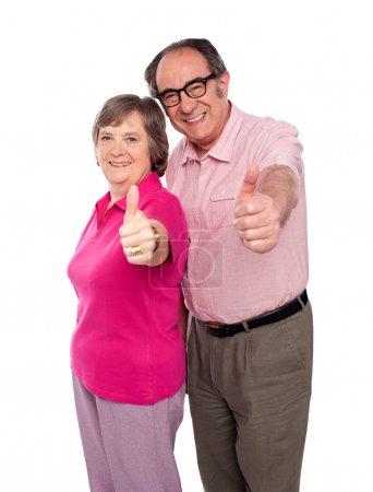 Photo pour Couple sénior gesticulant les pouces vers la caméra, isolé - image libre de droit