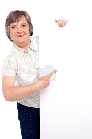 Photo pour Causal dame âgée pointant vers la plaque blanche - image libre de droit