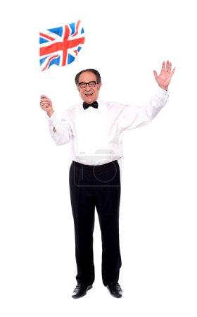 Photo pour Homme âgé élégant célébrant le succès et agitant le drapeau britannique - image libre de droit