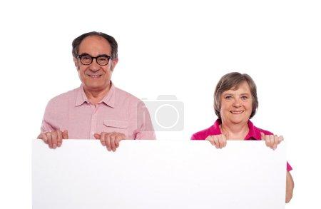 Photo pour Couple âgé affichant panneau d'affichage vierge isolé sur fond blanc - image libre de droit