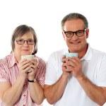 Romantic senior couple holding coffee mugs and smi...