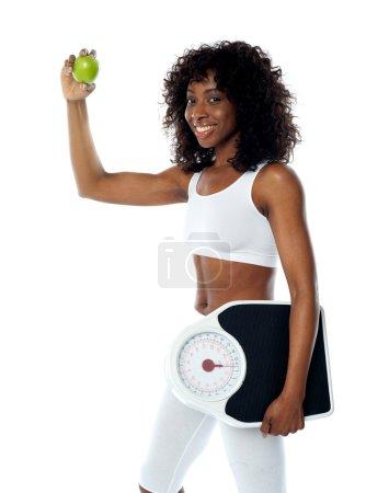 Photo pour Athlète tenant une pomme verte et une peseuse portant une tenue de sport blanche - image libre de droit