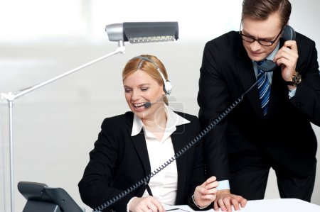 Photo for Male executive attending clients call while female secretary enjoys the conversation - Royalty Free Image
