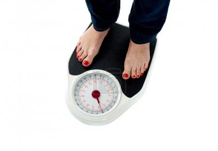 Photo pour Femme debout sur la balance, gros plan des jambes. Tout sur fond blanc - image libre de droit