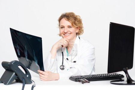 Foto de Cirujano sonriente sostiene Informe radiografía sentado en su clínica - Imagen libre de derechos