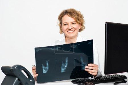 Foto de Cirujano experimentado mujer sosteniendo a los pacientes informe de radiografía y sonriendo a la cámara - Imagen libre de derechos
