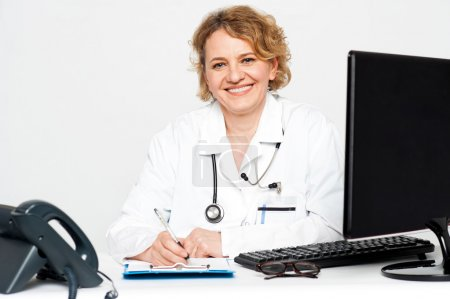 Photo for Smiling middle aged female doctor sitting in clinic writing on notepad - Royalty Free Image