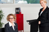 Woman handing over files to her female boss