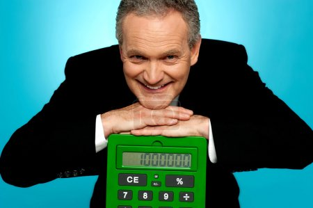 Aged corporate male resting face on big calculator