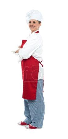 Foto de Vista lateral del chef femenino envejecido medio seguro posando con los brazos cruzados mirando - Imagen libre de derechos
