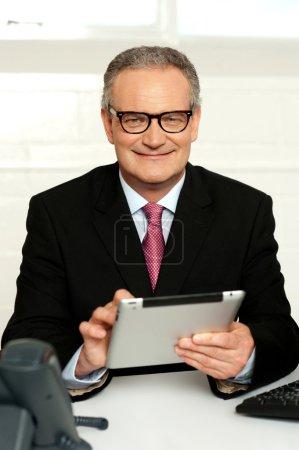 Senior Executive sitzt mit Tablet-PC in der Hand