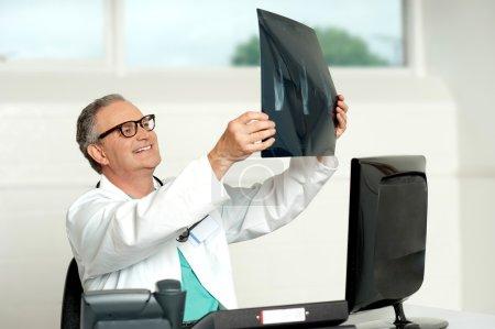 Foto de Cirujano Senior en vasos mirando el informe radiografía de un paciente - Imagen libre de derechos