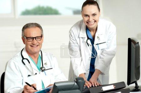 Foto de Equipo de médicos. ayudante femenina escribiendo en el teclado y el hombre escribiendo en portapapeles - Imagen libre de derechos