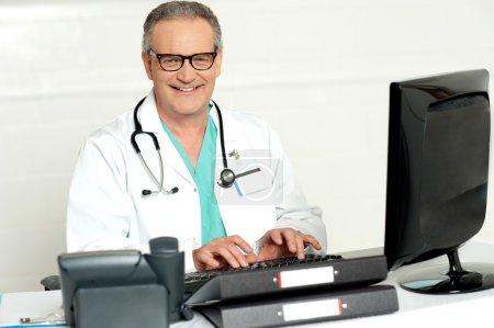 Foto de Doctor hombre envejecido en vasos trabajando en equipo, sonriendo a la cámara - Imagen libre de derechos