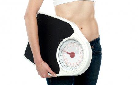 Photo pour Gros plan, femme portant un appareil de pesage. Image recadrée - image libre de droit