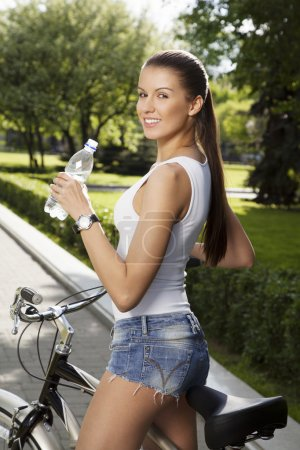 Girl with bicycle and bottle of water