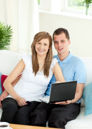 Enthusiastic couple using laptop smiling at the camera