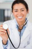 Krásný ženský lékař pomocí stetoskopu při pohledu na ca
