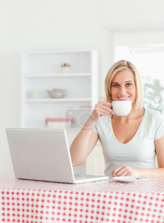 Woman drinking coffee with notebook in front of her