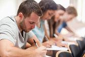 Vážné studenti sedí na zkoušku