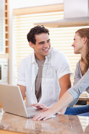 Smiling couple with laptop in the kitchen