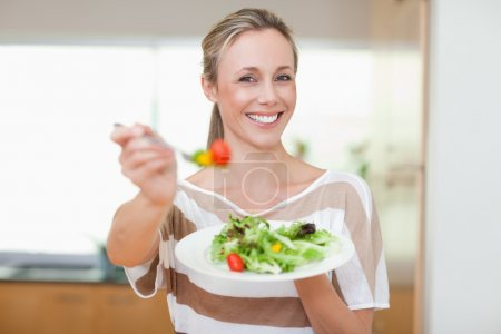 Woman offering healthy salad