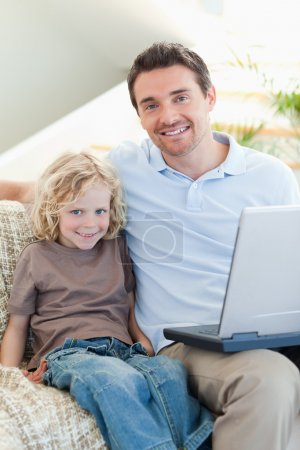 Father and son on sofa with laptop