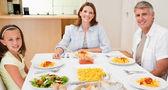 šťastná rodina sedí u jídelního stolu