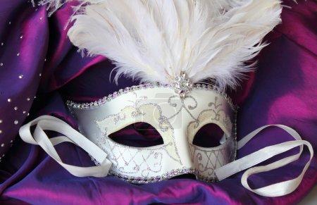 Photo pour Un masque de bal masqué mardi gras sur une robe en satin violet - image libre de droit