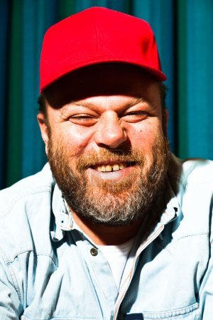 Man with beard and red cap. Portrait of a trucker....