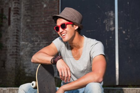 Urban asian man with hat, red sunglasses and skateboard sitting on stairs. Good looking. Cool guy. Wearing grey shirt and jeans. Old neglected building in the background.